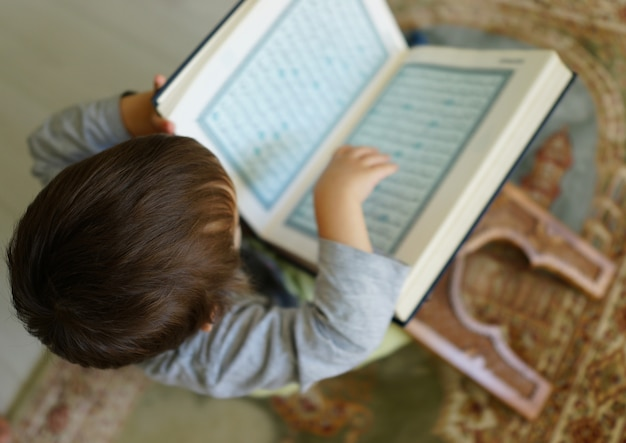Kid reading koran (the page is blurred) Premium Photo