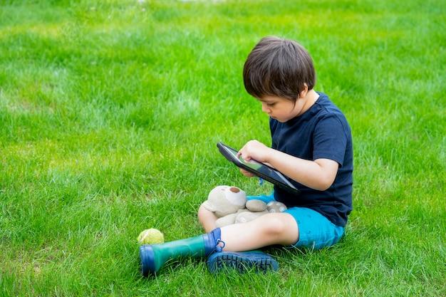 草の上に座って、タブレットでゲームをする子供 Premium写真