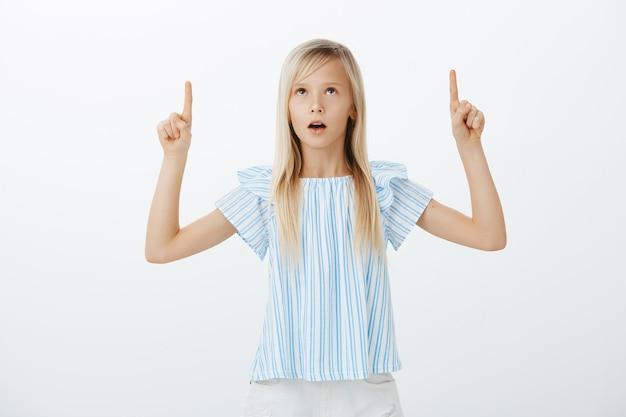 立っている子供は蜂の巣にまだ驚いています。ブルーのブラウスを着た愛らしい女性の子供に衝撃を与え、不思議に思った 無料写真