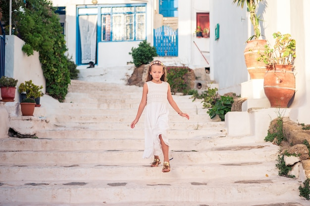Kid at street of typical greek traditional village with white walls and colorful doors on mykonos island Premium Photo