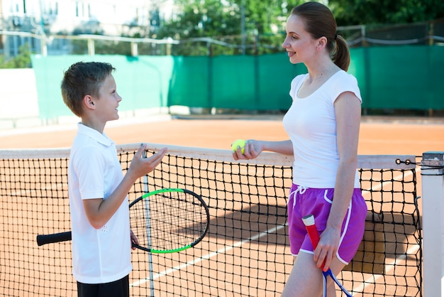 Kid talking with woman on the tennis field Free Photo
