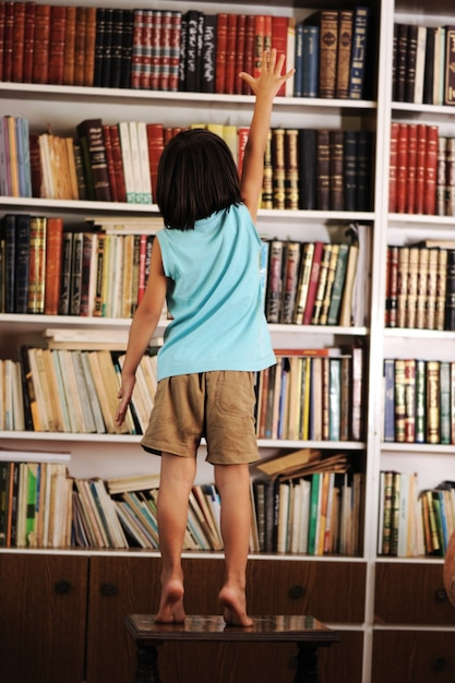 Kid trying to reach a book in the library Premium Photo