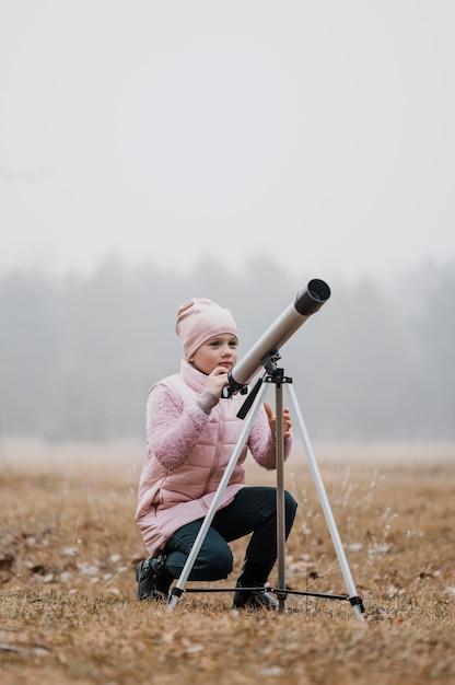 밖에서 망원경을 사용하는 아이 무료 사진
