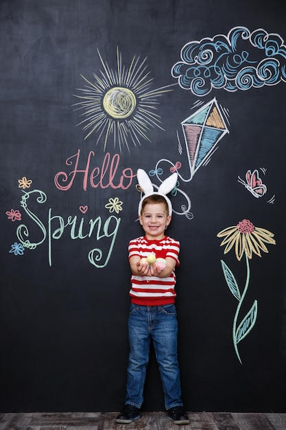 Kid wearing bunny ears and holding heap of easter eggs Free Photo