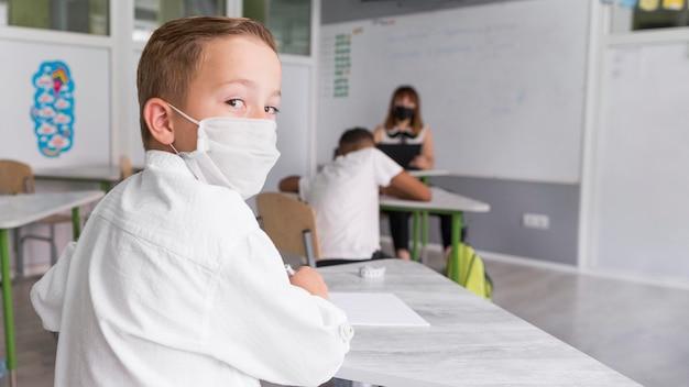 Bambino che indossa una maschera per il viso in classe Foto Gratuite