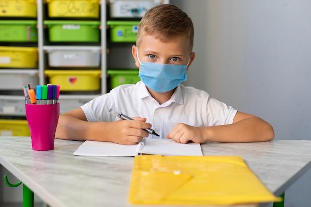 Bambino che indossa una maschera per il viso in tempo di pandemia Foto Gratuite