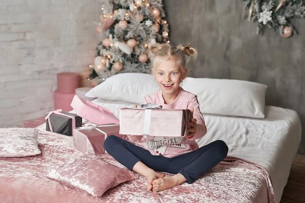 Kid wearing pajamas and opening christmas present Premium Photo