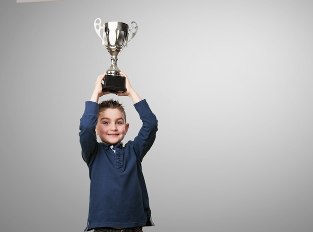 Kid with a trophy on his head Free Photo