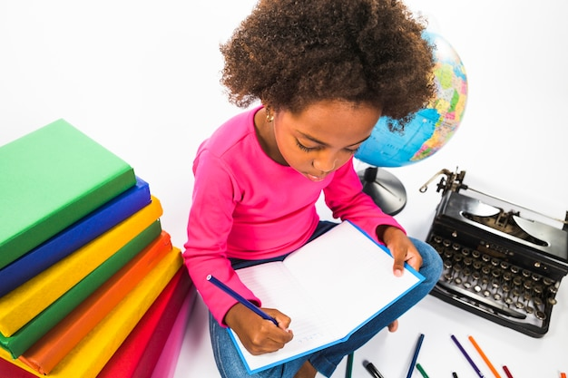 Kid writing in notebook in studio Free Photo