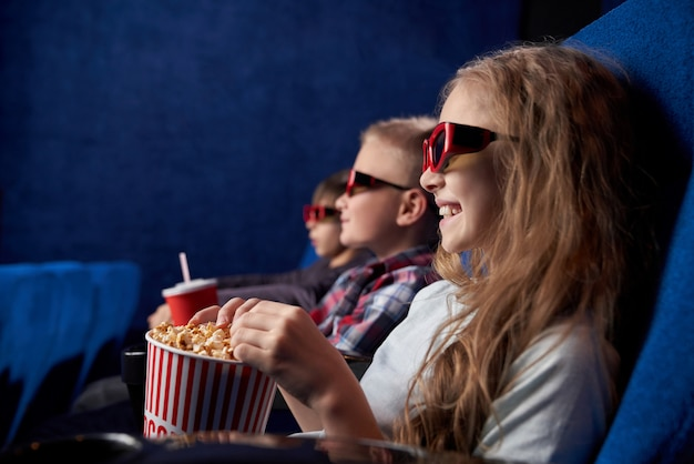 Kids in 3d glasses smiling, watching movie in cinema. Free Photo