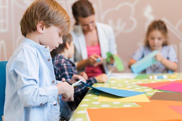 子供と先生が一緒に紙を切る 無料写真