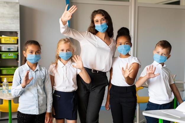 Дети и учитель позируют в медицинской маске Premium Фотографии