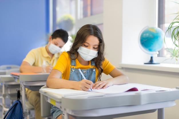 マスクと学校での子供たち Premium写真