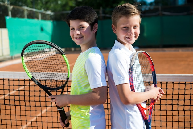 Kids back to back on the tennis court Free Photo