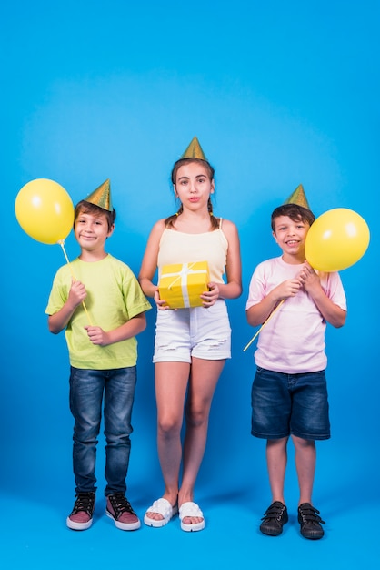 Kids in birthday hat holding yellow gift and yellow balloons against blue backdrop Free Photo