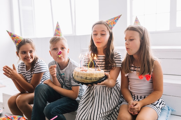 Kids blowing out birthday candles and having fun Free Photo