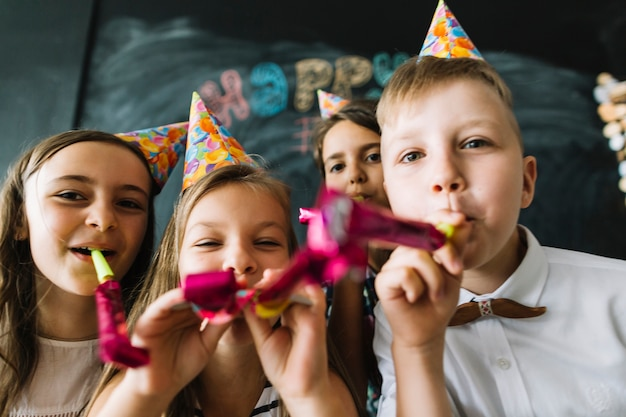 Kids blowing party horns at camera together Free Photo