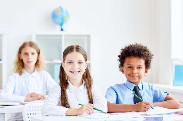 Kids by desks Free Photo