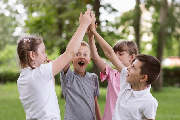 Kids cheering before playing a game Free Photo