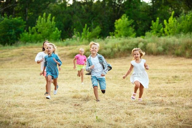 Kids, children running on meadow in summer's sunlight. Free Photo