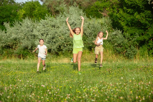 Kids, children running on meadow in summer's sunlight. Free Photo