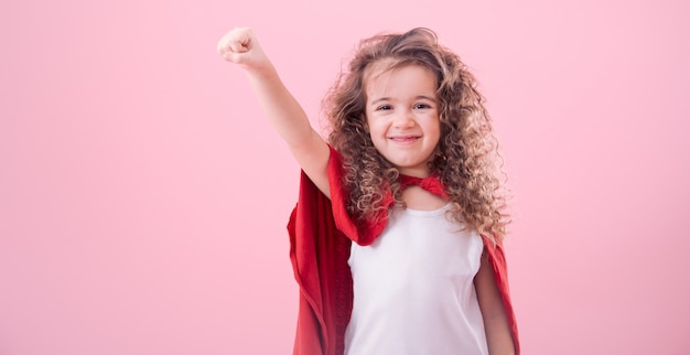Дети концепции, улыбающаяся девушка играет супер героя Бесплатные Фотографии
