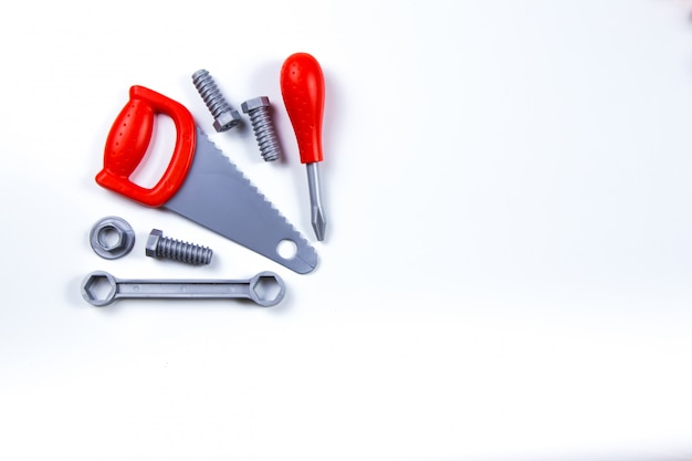 Kids construction toys tools: colorful screwdrivers, screws and nuts on wooden background. Premium Photo