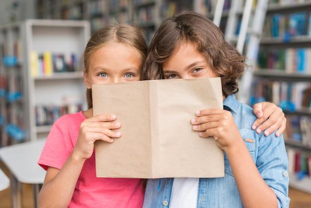 本で顔を覆っている子供たち 無料写真