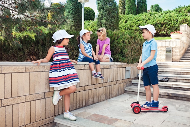 Concetto di moda per bambini. gruppo di ragazzi e ragazze adolescenti in posa al parco. bambini vestiti colorati, stile di vita, concetti di colori alla moda. Foto Gratuite