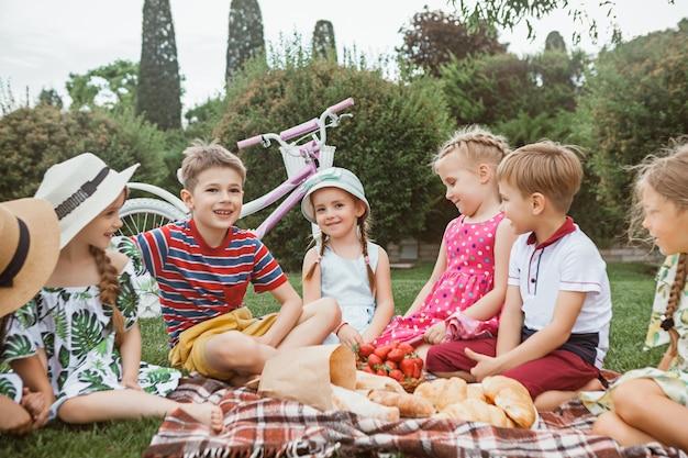 Concetto di moda per bambini. gruppo di ragazzi e ragazze adolescenti seduti all'erba verde al parco. bambini vestiti colorati, stile di vita, concetti di colori alla moda. Foto Gratuite