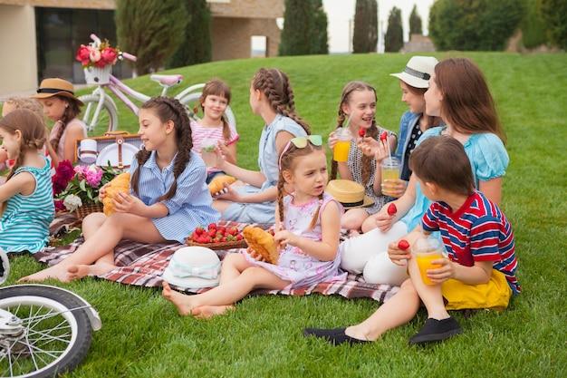 Concetto di moda per bambini. gruppo di ragazze adolescenti seduto all'erba verde al parco. bambini vestiti colorati, stile di vita, concetti di colori alla moda. Foto Gratuite