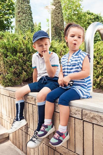 Concetto di moda per bambini. il ragazzo e la ragazza teenager che si siedono al parco. bambini vestiti colorati, stile di vita, concetti di colori alla moda. modelli caucasici Foto Gratuite
