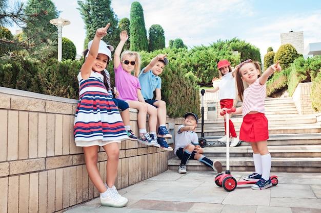 子供のファッションのコンセプトです。 10代の男の子と女の子が公園でポーズのグループ。子供たちのカラフルな服、ライフスタイル、流行色の概念。 無料写真