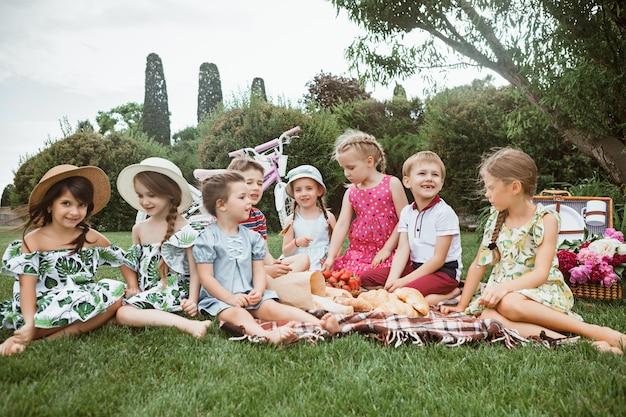 子供のファッションのコンセプトです。公園で緑の芝生に座っている10代の男の子と女の子のグループ。子供たちのカラフルな服、ライフスタイル、流行色の概念。 無料写真
