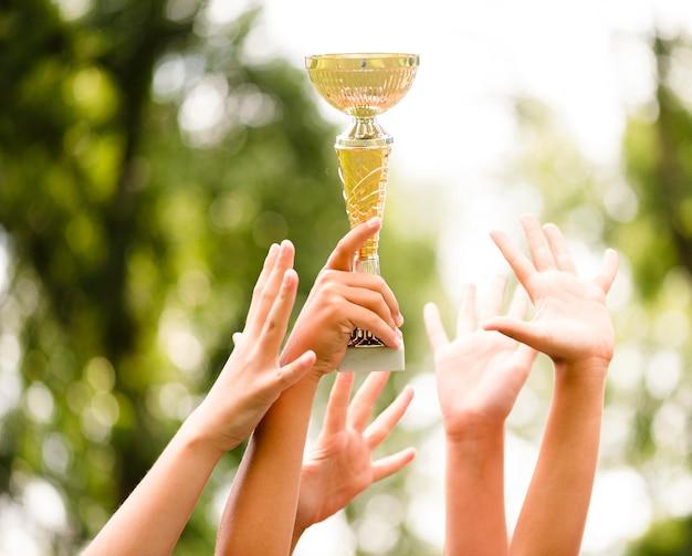 Kids getting a trophy after winning a football match close-up Premium Photo