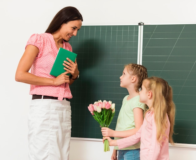 Дети дарят цветы своему учителю Premium Фотографии