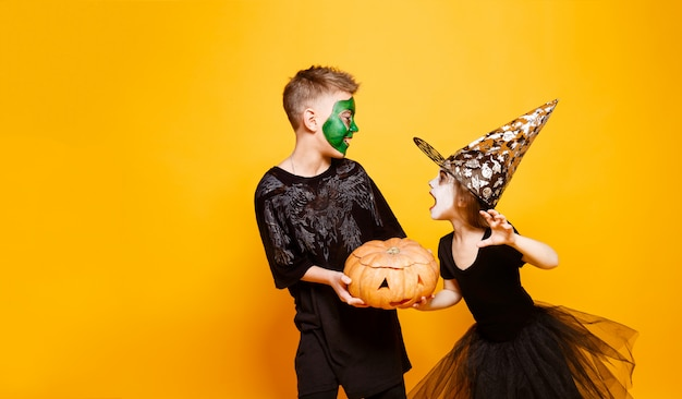 Kids in halloween costumes playing with pumpkin Premium Photo