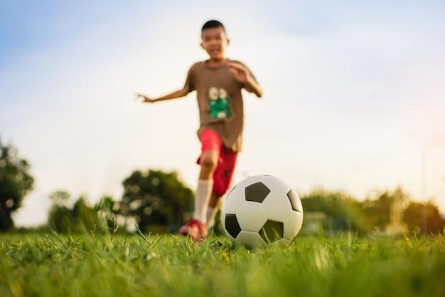 Дети веселятся, играя в футбол для упражнений Premium Фотографии