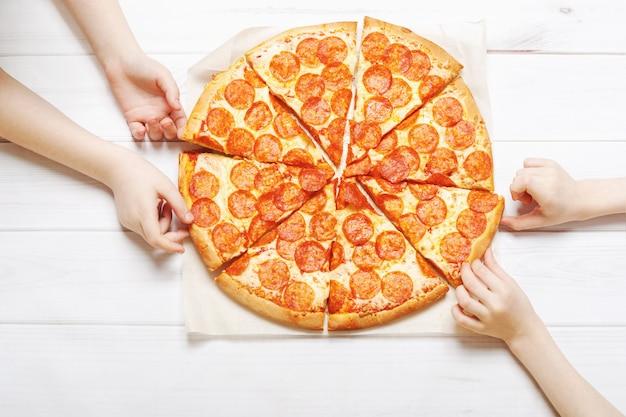 Kids holding a slice of pizza. Premium Photo