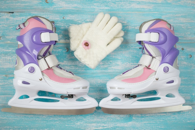 Kids ice skates with adjustable size and accessories on the wooden floor. Premium Photo