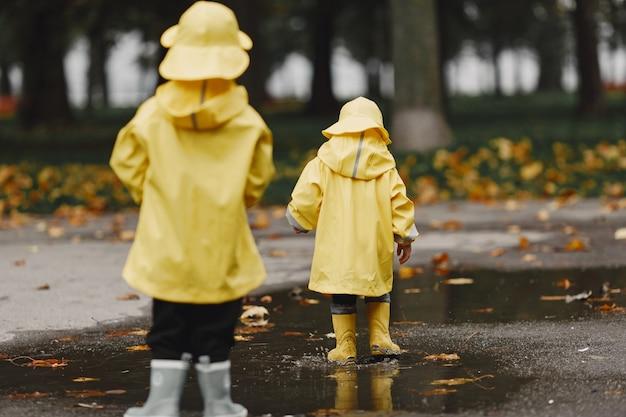秋の公園の子供たち。黄色いレインコートを着た子供たち。屋外で楽しんでいる人。 無料写真