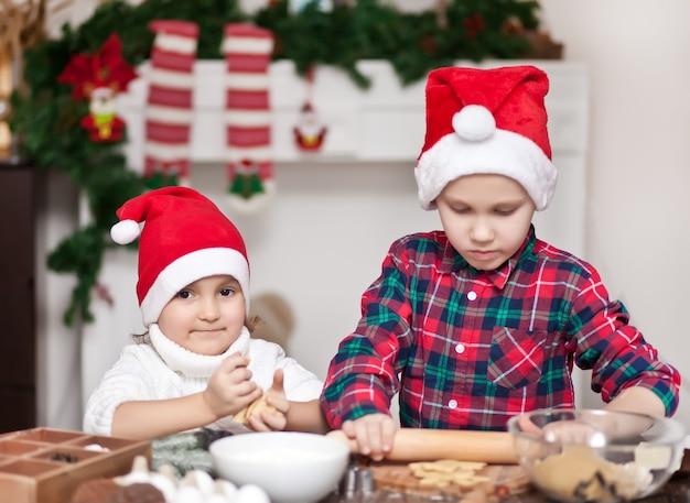 クリスマスのクッキーを焼くサンタの帽子の子供たち Premium写真