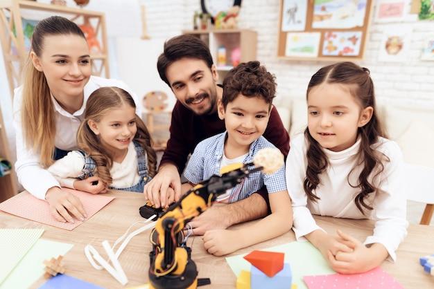 幼稚園の子供たちはロボットと一緒に遊んでいます。 Premium写真