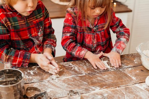 Bambini che fanno insieme i biscotti di natale Foto Gratuite