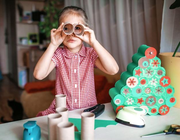 自宅でトイレットペーパーロールで手作りのクリスマスアドベントカレンダーを作る子供たち Premium写真