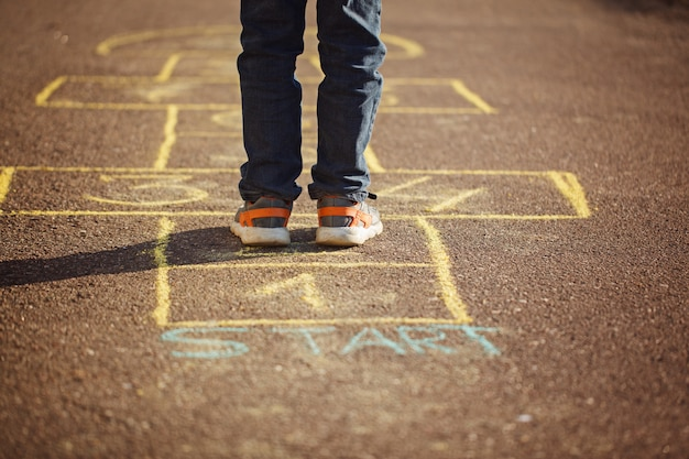 Kids playing hopscotch on playground outdoors. hopscotch popular street game Premium Photo