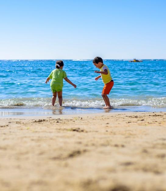 Kids playing at sea shore under sunlight Premium Photo
