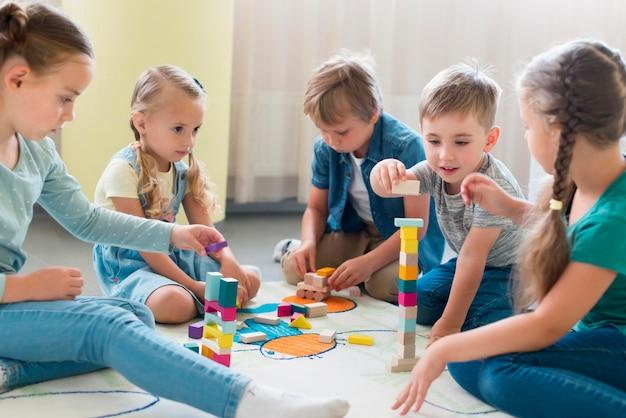 幼稚園で一緒に遊ぶ子供たち Premium写真