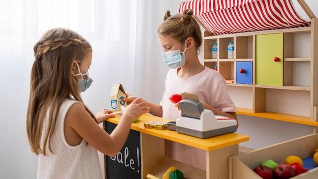 Bambini che giocano insieme in casa indossando maschere mediche Foto Gratuite