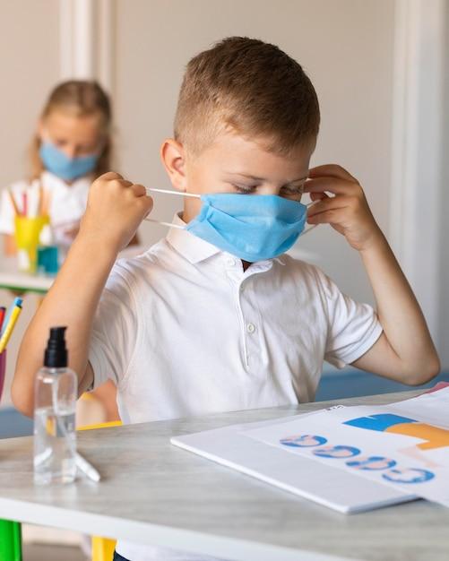 Kids putting on his medical mask Free Photo